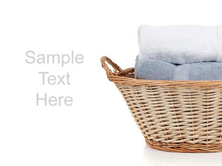 mimbre: Toallas de blancos y azules en una canasta de mimbre lavander�a sobre un fondo blanco con espacio de copia
