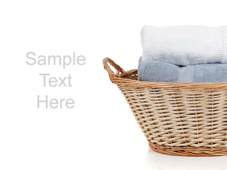 White and blue towels in a wicker laundry basket on a white background with copy space