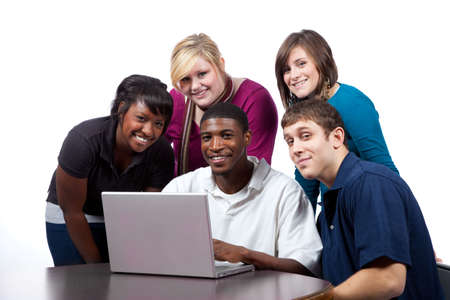 A group of multi-racial college students sitting around a computer