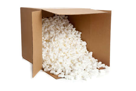 A brown, corrugated cardboard moving box with packing peanuts on a white background