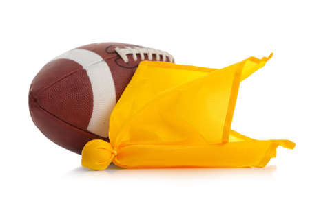 Football and yellow penalty flag on a white background