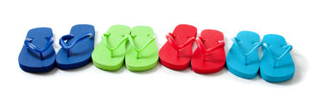 Row of blue, green, red and turguoise flipflops on a white background