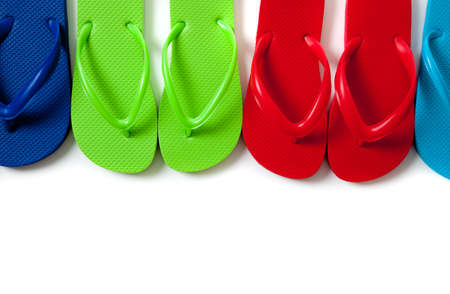 flops: Row of blue, green, red and turguoise flipflops on a white background