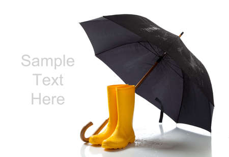 umbrella rain: A pair of yellow rainboots and a black umbrella on a white background with copy space