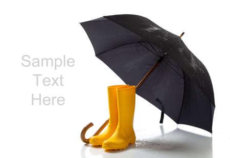 lluvia paraguas: Un par de rainboots de color amarillo y un paraguas negro sobre un fondo blanco con espacio de copia
