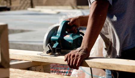 hardened: A man cutting wood using a circular saw Stock Photo