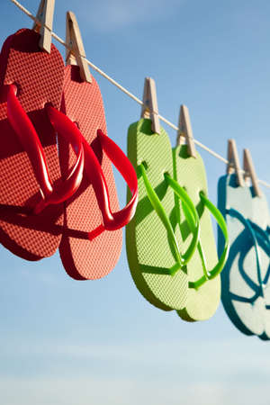 Red, green and blue flipflops hanging on a line with a sky background 스톡 콘텐츠