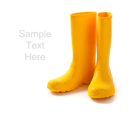 A pair of yellow rainboots  on a white background with copy space