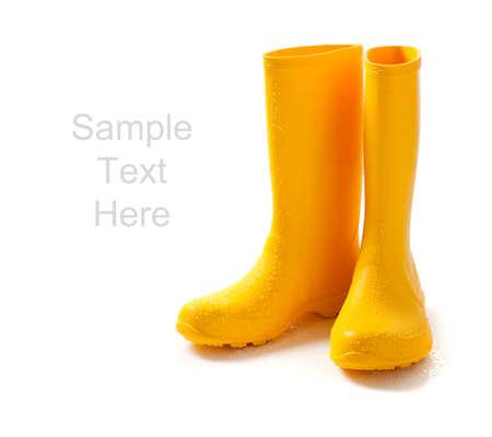 botas de lluvia: Un par de rainboots amarillo sobre un fondo blanco con espacio de copia  Foto de archivo