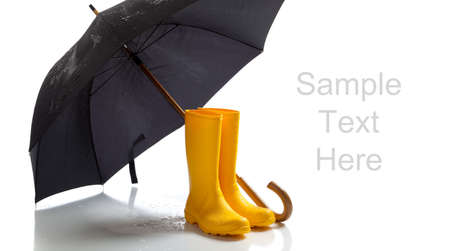 A pair of yellow rainboots and a black umbrella on a white background with copy space Stock fotó - 6843161