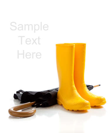 A pair of yellow rainboots and a black umbrella on a white background with copy space photo