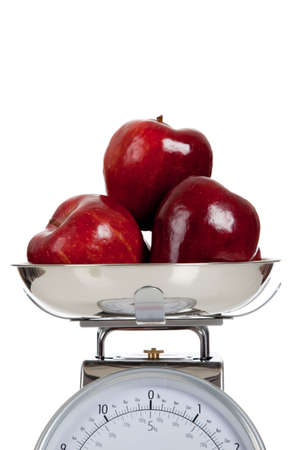 Red apples on a scale with a white background