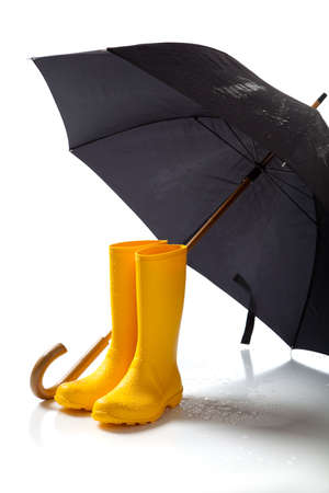 A pair of yellow rainboots and a black umbrella on a white background