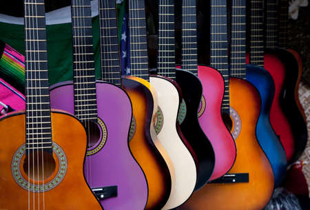 guitars: A row of various multi-colored mexican guitars