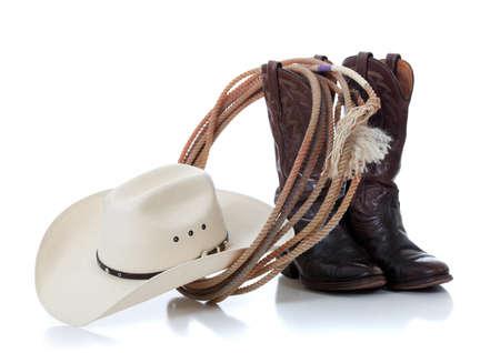 country: Een witte cowboyhoed, bruin lederen laarzen en lariat op een witte achtergrond Stockfoto