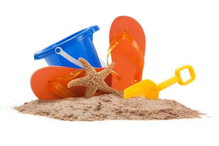 starfish beach: Beach scene with blue pail, orange flip-flops, starfish and a yellow shovel Stock Photo