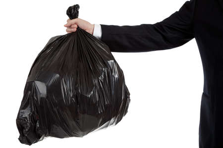 A business mans arm holding a black bag of trash Stock Photo