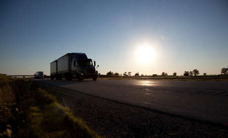 A semi-trailer drving down the highway with the sky and sun in the background