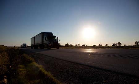 remolque: Un semirremolque drving por la autopista con el cielo y el sol en segundo plano