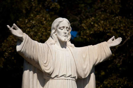 outstretched: Statue of Jesus with outstretched arms in an outdoor garden