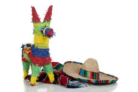 traje mexicano: Serape mexicano, sombrero y piñata sobre un fondo blanco con espacio de copia