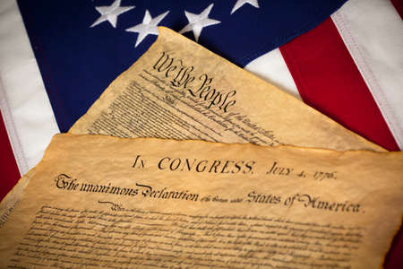 the United States Constitution and Declaration of Independence on a Betsy Ross Flag background