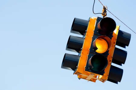 traffic signal: A yellow light traffic signal with blue sky copy space Stock Photo