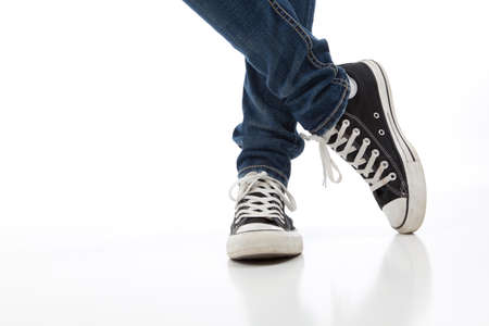 Person wearing Vintage tennis shoes on a white background with skinny jeans