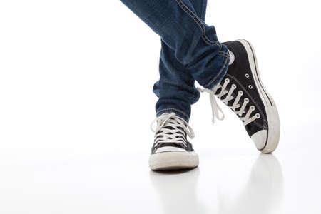 skinny jeans: Persona con zapatos vintage de tenis sobre un fondo blanco con jeans ajustados