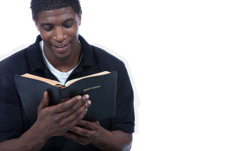 A young black man reading the Holy Bible on a white background Stock Photo