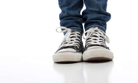 Person wearing vintage tennis shoes on a white background with skinny jeans photo