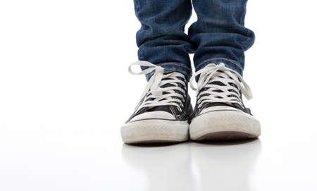 skinny jeans: Persona con zapatos cl�sicos de tenis sobre un fondo blanco con jeans ajustados Foto de archivo