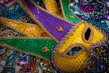 mardi gras mask: A yellow Mardi Gras jester mask and beads