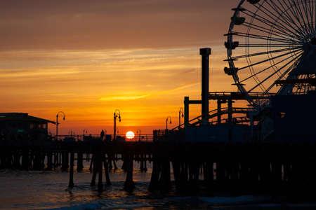 サンタモニカー、カリフォルニア州の日没で桟橋