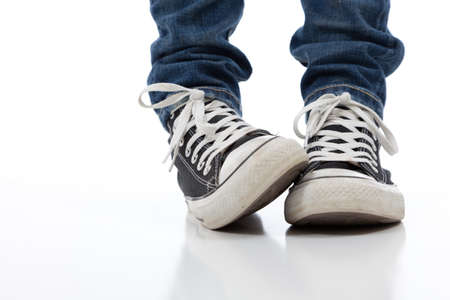 Girl wearing classic vintage looking sneakers on a white background, nervousness, shyness