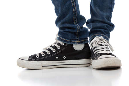 A pair o f vintage looking, athletic shoes and skinny jeans on a white background with copy space
