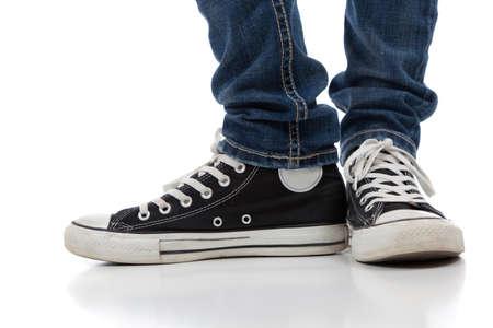 skinny jeans: Un par de zapatos de �poca, de aspecto atl�tico y jeans ajustados sobre un fondo blanco, con copia espacio