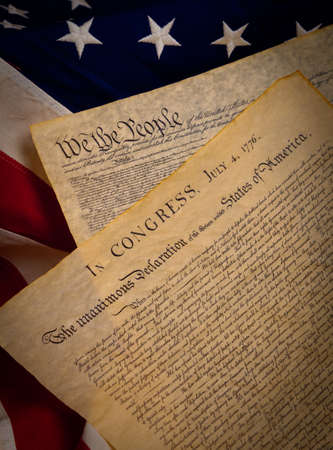 A copy of the constitution and the declaration of indepenedence of the United States on a flag background