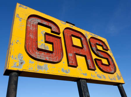 old sign: A vintage, antique, gasoline sign in front of a blue sky on  a sunny day