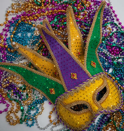 A yellow Mardi Gras jester mask and beads photo