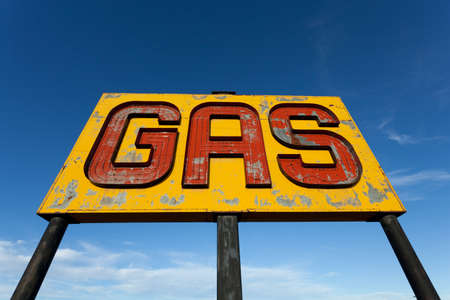 A vintage, antique, gasoline sign in front of a blue sky on  a sunny day photo