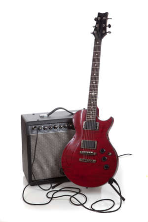 A electric guitar on a stand with an amplifier and cords on a white background with copy space