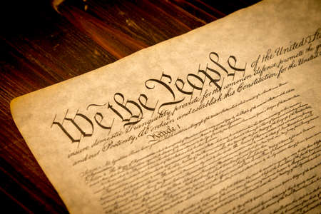 declaration: The Constitution of the United States of America on a wooden desk