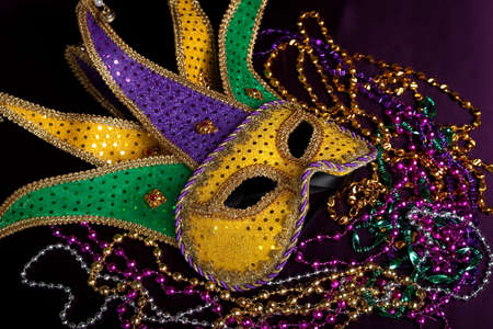 A mardi gras jesters maske with purple, gold and green beads on a black background photo