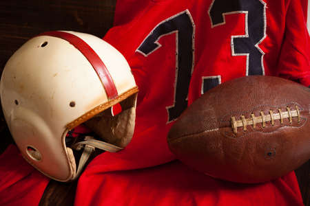 old items: A grouping of vintage, antique american football items including an helmet, jersey, and old leather football