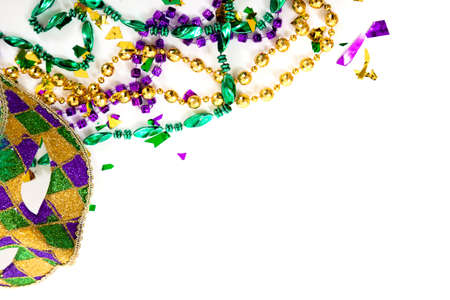 紫色、金と緑のマルディグラのマスクとコピー領域の白い背景の上にビーズ