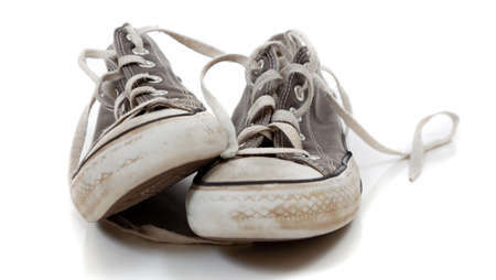 a pair of worn out gray retro sneakers on a white background