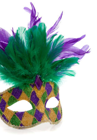 A purple, gold and green Mardi gras mask with feathers on a white background