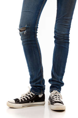 A pair of skinny legs in jeans and retro black sneakers on a white background