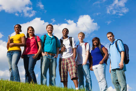 A group of diverse college students/friends outside on a hill with a sky background Stockfoto
